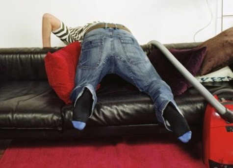 Young man vacuuming behind sofa, rear view